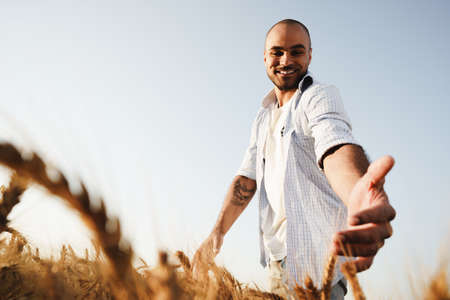 Young man standing in wheat field on sunset