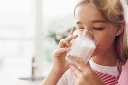 Blonde teen girl drinking glass of milk at home in kitchen Stock Photo
