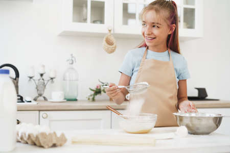 Portrait of a little blonde teen girl wearing apron in kitchen