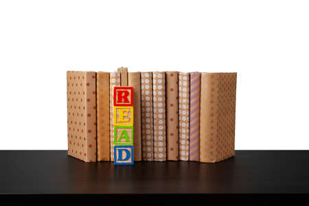 Stack of books on wooden table against white background