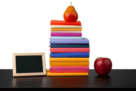 Stack of books and apple on tabletop against white background