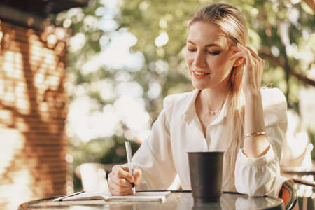 Pensive young businesswoman sitting in outdoor cafe and making notes