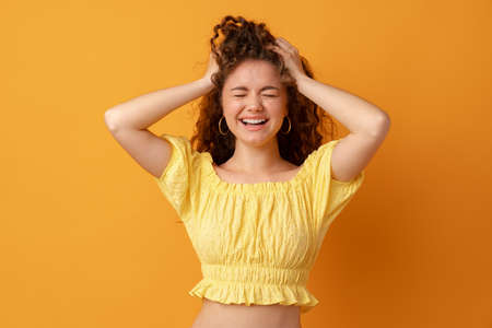 Concerned, stressed, regretful young woman holding her head Stock Photo