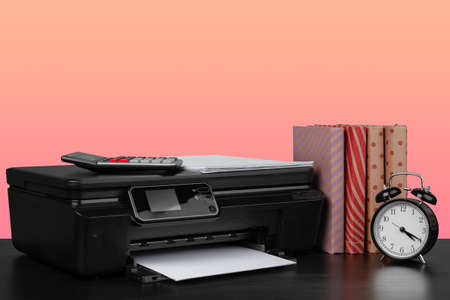 Compact home laser printer against pink background