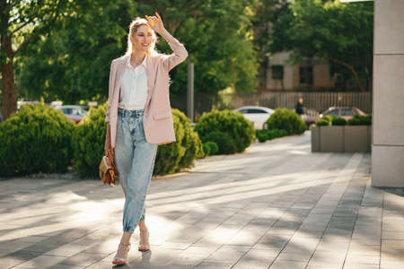 Stylish young businesswoman walking on the city street on sunny day
