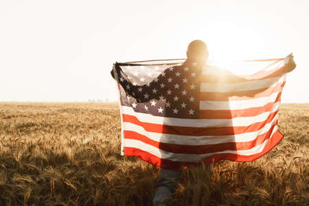 Young man holding American flag on back while standing in wheat field