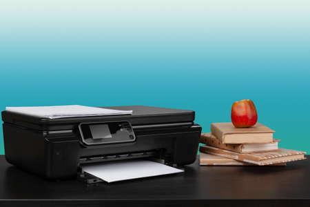 Home laser printer on desk against green background