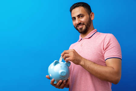 Handsome very excited hispanic man holding piggy bank against blue background Stock Photo