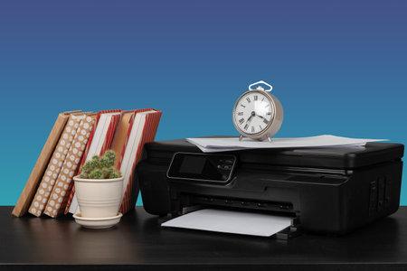 Compact laser printer on black desk against blue background