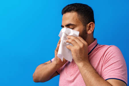 Young man in pink shirt with allergy or cold, blowing his nose in a tissue against blue background Stock Photo