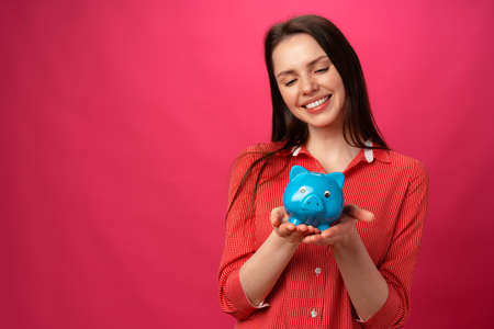 Happy smiling young woman holding blue piggy bank against pink background