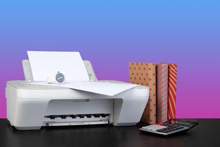 Home laser printer on desk against purple background