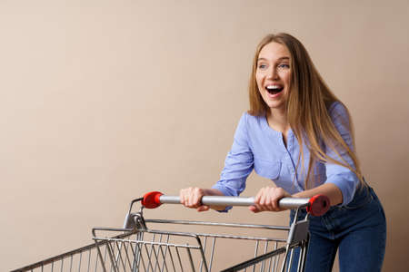 Young cheerful woman with empty shopping cart on beige background