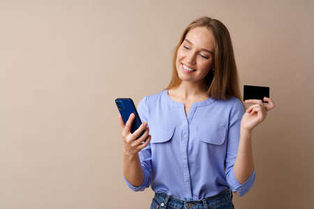 Happy young woman holding smartphone and credit card against beige background Stock Photo