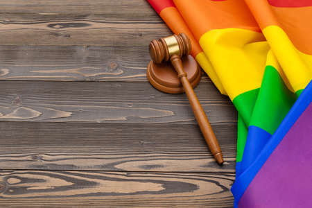 Woden judge mallet symbol of law and justice with lgbt flag in rainbow colours on wooden background Stock Photo