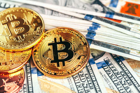 Golden bitcoin coins on a paper dollars money Stock Photo