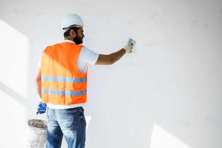 Plasterer in workwear smoothing wall surface of building indoors