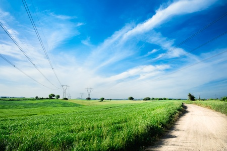 clean street: Two overhead lines towers across a landscape with cornfields on spring and a dirt street