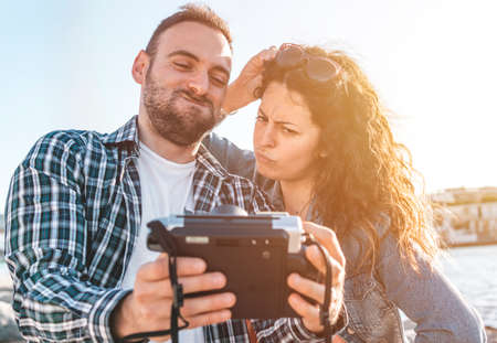Young loving couple on vacation at the beach takes a funny selfie with an instant camera - Boyfriend and girlfriend share their moments of relaxation by taking a photo - love and carefree concept - warm filter Foto de archivo