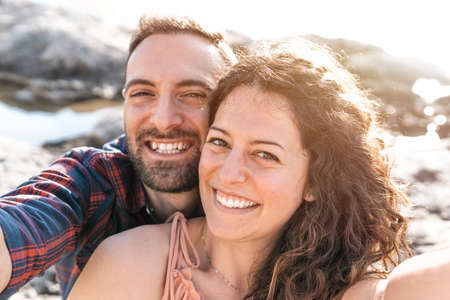 Young loving couple on vacation at the beach takes a selfie - Boyfriend and girlfriend share their moments of relaxation by taking a photo - love and carefree concept - warm filter