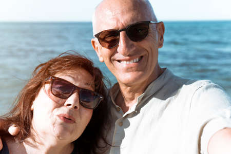 Middle-aged couple takes a selfie on the beach during a vacation - Happy elderly couple having fun in their free time - Active retirees having fun traveling the world concept - flare on background
