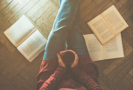 Top view of a girl drinking a cup of coffee with books on the wooden floor - home comfort and coziness in autumn concept