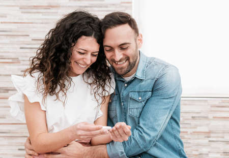 Portrait of a young couple reading hugging pregnancy test result - married couple is happy to expect a baby - warm flare on background