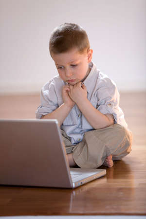 Child concentrated on a computer at home photo