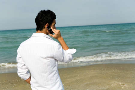 call of nature: Man with mobile phone alone at the beach Stock Photo