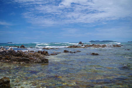 A view of the Indian Ocean (Philippines) with many jagged rocks jutting out of its waters. There are slight waves in the sea. Its a sunny summer day and there are few clouds in the blue sky. 写真素材