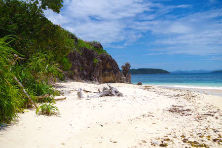 A small, deserted island in the Philippines archipelago. The island has a beautiful sandy beach and a patch of palm trees growing near big jagged rock. Its a calm sunny day and the sky is very blue. 写真素材