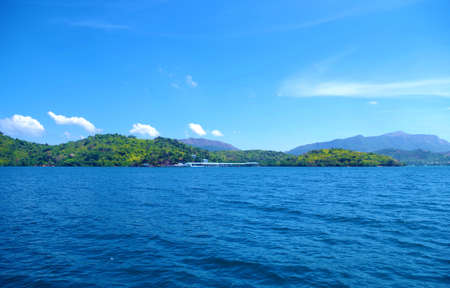 A small forested island in the Philippines archipelago. Isle is surrounded by the blue, calm waters of the ocean and azure, clear sky. There are few clouds, day is very bright and sunny.