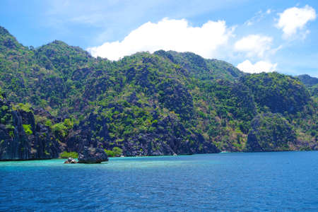 A big rocky island in the Philippines archipelago. The water of the ocean is calm and rippling slightly. The sky is clear and blue. It's a sunny warm summer day. Standard-Bild