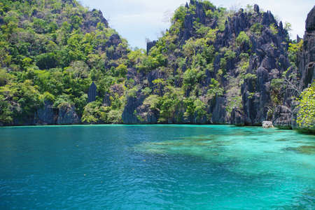 A big rocky island in the Philippines archipelago. The water of the ocean is calm and rippling slightly. The sky is clear and blue. It's a sunny warm summer day. Stock Photo