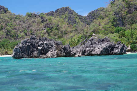 A big, jagged rock jutting out of the sea just of the coast of one of the islands in the Philippines. The rock is sparsely covered by shrubberies and surrounded by a small, beautiful reef. 写真素材