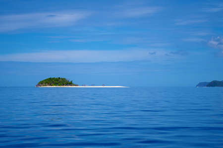 A shot of a very calm sea on a sunny day. There are few scattered clouds in the sky. On the horizon we can see a small island, overgrown with palm trees and sporting an inviting, sandy beach
