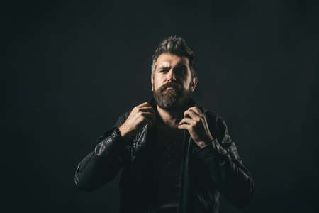 Fashion man. Handsome serious bearded male model portrait wear black leather jacket. Attractive bearded hipster man fixes collar leather jacket. Seasonal fashion. Copy space to advertise.