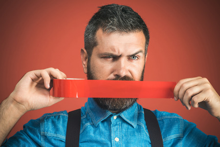 Businessman silenced with duct tape over his mouth. Bearded man with wrapping adhesive tape around mouth. Unhappy man in denim shirt covered mouth with red insulating tape. Isolated on red background.