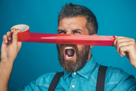 Screaming bearded man glued his nose insulating tape. Casual man in denim shirt with duct tape covering his nose. Emotions, facial expressions - shouting businessman covered by face red adhesive tape.