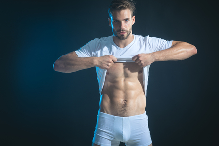 Very sexy young man showing abdominal muscles with taking off his t-shirt, isolated on a black background. Handsome, brutal macho in white boxer shorts, looking at camera.