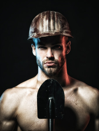 Sexy worker concept. Male laborer with shovel. Builder, repairman, engineer, constructor, construction worker with spade. Industrial worker protective helmet with spade. Labour, industry, repair, job. Standard-Bild