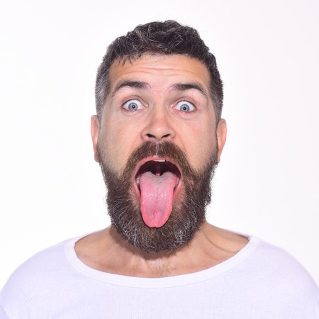 Bearded man with long beard and moustache shows tongue. Portrait of handsome bearded man on white bsckground. Emotions. Emoji. Funny faces. Archivio Fotografico