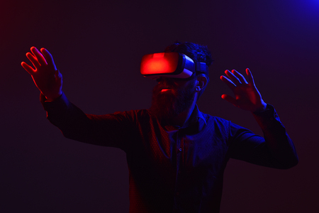 Future technology. Scared man in virtual reality glasses. Future. Men using VR headset. Virtual reality goggles. Virtual reality device. Lights. Isolated on black background.