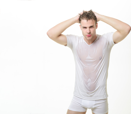 Sexy muscle man in underwear&wet white t-shirt. Masculinity, power, strength. Sexy guy with muscular body in wet shirt&boxer shorts. Male underwear fashion concept. Man in white underwear. Copy space. 版權商用圖片