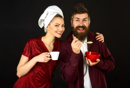 Loving couple having breakfast. Romantic couple eating. Woman hug a handsome smiling bearded man. Isolated on black background. Cute couple has breakfast at home.