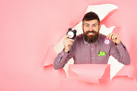 Happy bearded man looking through hole in pink paper and holds clocks. Saving time. Business concept. Saving time concept. Bearded man peeking through hole in pink paper. Copy space for advertise.
