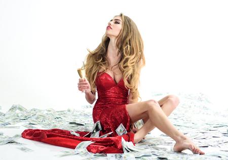 Mujer orgullosa en elegante vestido rojo sostiene una copa de champán y se sienta en los billetes. Mujer rica Concepto de negocio. Concepto de ahorro de dinero. Concepto de éxito empresarial. Concepto de dinero digital. Finanzas.