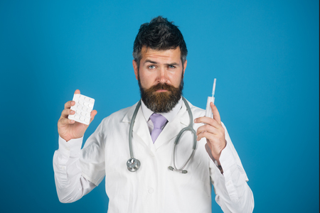 Bearded doctor, physician with pills, syringe, injection in hand. Treatment diseases with modern methods. Homeopathic. Advertisement of quality medicines. Medical drug for health, healthcare.