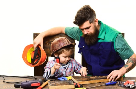 Father teaches son repair case. Son and father repairing together. Bearded man with little assistante. Boy works with screwdriver. Repair and engineering education. Dad teaches little son to use tools