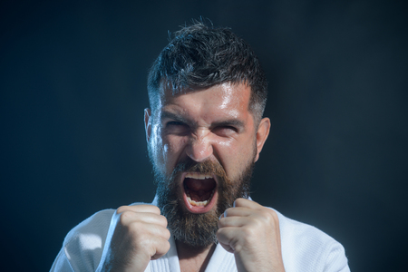 Strong, angry, bearded man dressed in kimono, shaking fist, portrait a screaming boxer. Brutal bearded boxer, ready to fight. Boxing, workout, muscle, strength, power - sport concept. Stock Photo